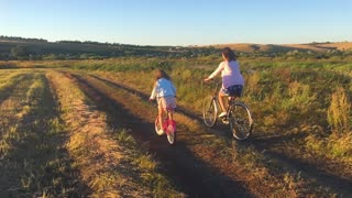 Mother with daughter on bicycles in a meadow. Family on bicycles in nature. The concept of the family.