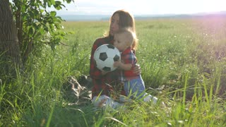 Mother with her little son are sitting on the grass in the park and playing with a football ball. Happy family with football ball on a field.