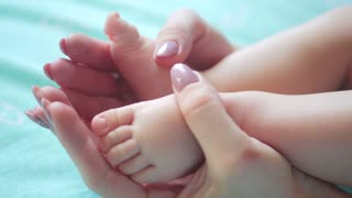 mother's hands holding small baby's feet