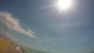 Motor hang glider fly over the beach on a sunny summer day.