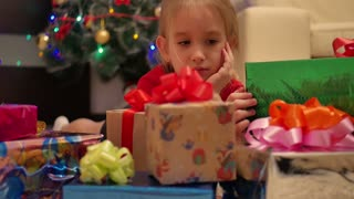Not happy little girl with christmas gift box.