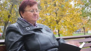 Old age, retirement and people concept - happy senior woman reading book sitting on bench at autumn park. Side view at elder woman in glasses reading book on bench in autumn park.