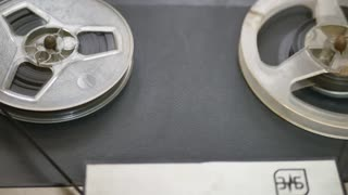Old coil tape recorder with magnetic tape on reels. Reel with recording tape close up in reel-to-reel recorder.