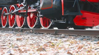 Old locomotive wheels close up. Detail of steam locomotive, side profile view, wheels, rods.