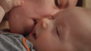 Parenthood concept - happy mother kissing smiling baby. Top view of mother kissing her infant baby in bed.