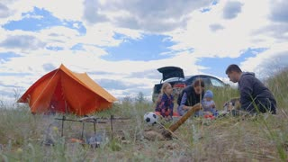 Parents and kids having a picnic and they are going to stay overnight in a tent. Traveler woman and children relaxing, playing outdoors near camping tent. Family holidays, leisure activity in forest.