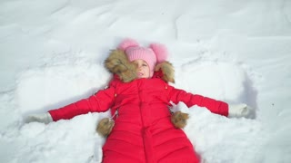 Portrait of a beautiful young girl laying down on a frozen snow lake moving her arms and legs up and down creating a snow angel figure, playing games during a sunny winter vacation.