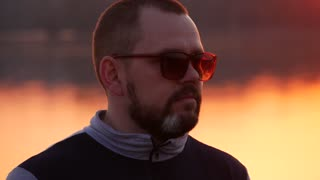 Portrait of a young bearded man in sunglasses on sunset background.
