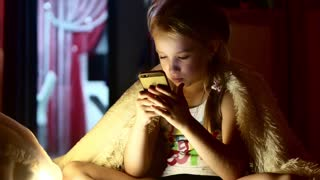 Portrait of smiling teenage girl lying under blanket and watching online content on her smartphone at night - hiding under the blanket.