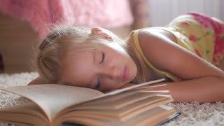 Portrait sad schoolgirl does not want to study and read a book. A sweet blonde girl is sleeping on a book, she is tired when she did her homework.
