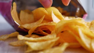 Potato Chips In Package Rotating. Open package of potato chips on the table and rotates. Close-up of yellow delicious chips randomly lying on a table.