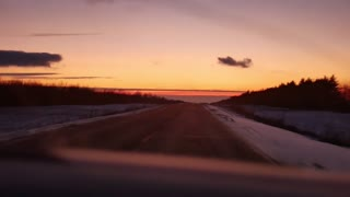 POV shot view from car driving on asphalt road in countryside during sunset.