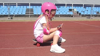 Pretty little girl learning to skateboard outdoors on beautiful summer day. Fashionably dressed girl, learn to skateboard on the stadium's treadmill. Uses a mobile phone.