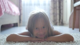 Pretty little girl lying on floor and smiling.