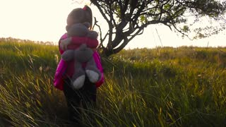 Pretty smiling little girl holding teddy bear. Little girl with teddy bear on nature. Beautiful little girl and teddy bear in park.