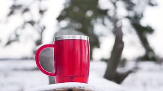 Red mug of tea on a wooden branch in the forest in the winter morning