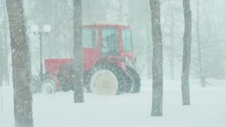 Red tractor cleans the road from the snow in the park