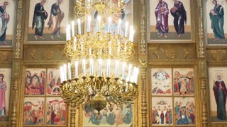 Russian orthodox church inside. Golden big chandelier close up and religious frescoes as background.