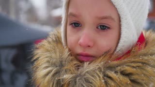 Sad girl in warm clothes outdoor in winter.