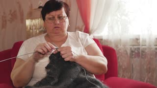 Senior woman knitting a scarf from natural goat hair with needles at home.