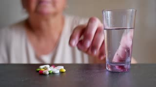 senior woman taking pills at home