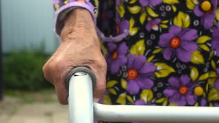 Senior woman using a walker. An elderly senior adult using a walker to help her mobility. Focus is on the hand.