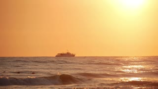 Ship silhouette in rough seas on sunset background.