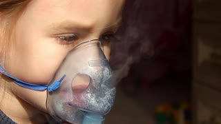 Sick girl with a sore throat makes inhalation with a mask on his face. Sick patient heals itself nebulizer.