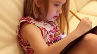 Side view of creative young girl drawing in a jotter while sitting on sofa at home. The concept of imagination, creating an image