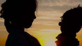 Silhouette a girl with doll on mountain and sky sunset. Concept big dream.