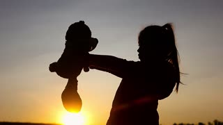 Silhouette a girl with teddy bear on mountain and sky sunset. Concept big dream.