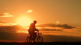 Silhouette biker lovely family on the meadow at sunset time. Silhouette of mother and baby biking at sunset. Lifestyle Concept.