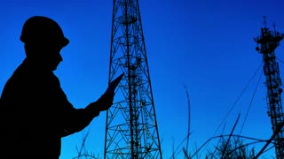 Silhouette engineer working on digital tablet, with satellite dish telecom network on telecommunication tower in sunset.