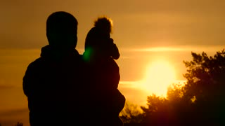 Silhouette father and little son at sunset. Happy family.