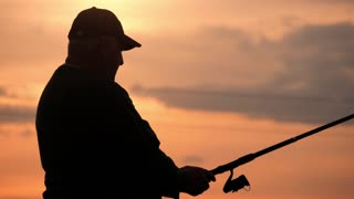 Silhouette fisherman throwing fishing rod in river on background evening sunset. Beautiful evening sunset during fishing on river. Sport hobby fishing.