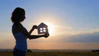 Silhouette girl with paper house as a symbol. The concept of family happiness.