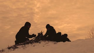 Silhouette group of people next to campfire at sunset. Two tourists travel in winter.