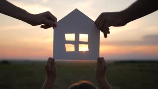Silhouette hands family with paper house at sky sunset background.