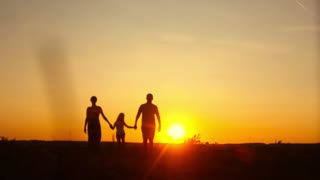 Silhouette, happy child with mother and father, family at sunset, summertime. Concept of friendly family.