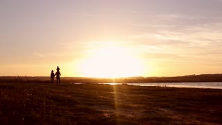 Silhouette, happy child with mother and father, family at sunset, summertime. Run, raising baby up in the air, hugs, love, playing.