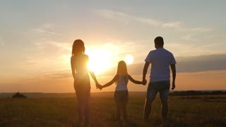 Silhouette, happy child with mother and father, family at sunset, summertime.