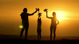 Silhouette happy family playing at the field at the sunset time. People having fun on the nature. A jigsaw puzzle piece isolated with sunset background. Concept of the kid is ready to go to school.