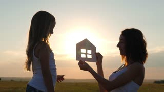 Silhouette happy mother and daughter with dream house. Paper house as a symbol. The concept of family happiness.