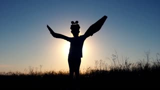 Silhouette little girl with cardboard boxes of wings against the sky dream of flying. Pretending to be a pilot for a craft, imagination or exploration concept. Imagination and freedom concept.