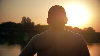 silhouette man bodybuilder against the sky, sunset and the river, athlete body silhouette during vacation, healthy lifestyle concept