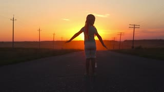 Silhouette of a beautiful girl standing against a sunset on the road, hands like wings for a flight. The concept of dreams is to learn to fly and freedom.