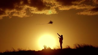 Silhouette of a happy family playing a kite. Grandpa and little girl are playing at sunset with a kite.