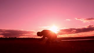Silhouette of a man praying at sunset concept of religion. Image of silhouette man praying with sunset background