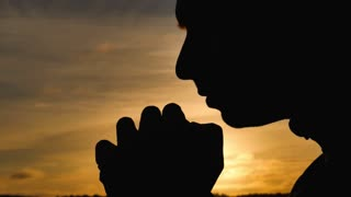 Silhouette of a man praying at sunset concept of religion. Silhouette man close up praying with sunset background.