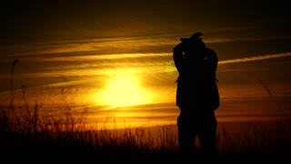 Silhouette of a man with a backpack against bright sky sunset. Sun goes down. Travel Concept. Slow video tourist go travel nature outdoors lifestyle.
